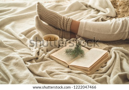 Cozy winter evening , warm woolen socks. Woman is lying feet up on white shaggy blanket and reading book. Cozy leisure scene. Text in book is unreadable. Woman relaxing at home. Comfy lifestyle. #1222047466