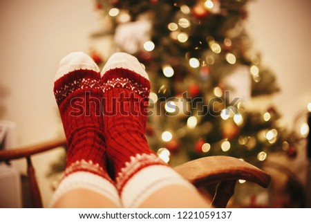 cozy winter holidays. warm atmospheric moment. festive socks on old wooden chair on background of golden beautiful christmas tree with lights in festive room. relax time