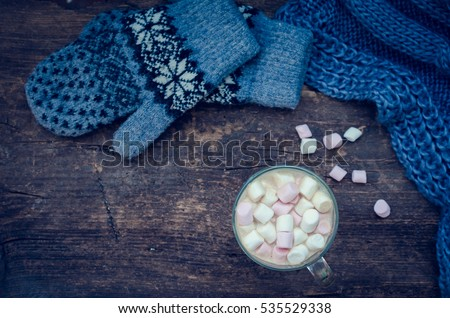 Cozy winter home background, glass of hot cocoa with marshmallow, warm knitted scarf and mittens on an old wooden board background with space for text. Christmas drink. Top view. Copy space. #535529338