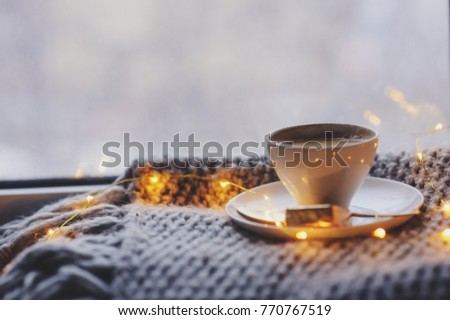 cozy winter or autumn morning at home. Hot coffee with gold metallic spoon, warm blanket, garland and candle lights, swedish hygge concept. #770767519