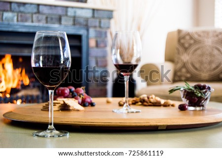 Cozy winter scene. Red wine and a snack platter with grapes, salted cracks, nuts and olives on a wooden board with a fire in a fireplace in the background.