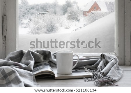 Cozy winter still life: mug of hot coffee and opened book with warm plaid on vintage windowsill of cottage against snow landscape with snowdrift from outside. #521108134