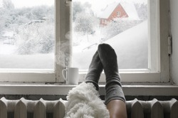 Cozy winter still life: woman legs in warm woolen socks under shaggy blanket and mug of hot beverage on old windowsill against snow landscape from outside.