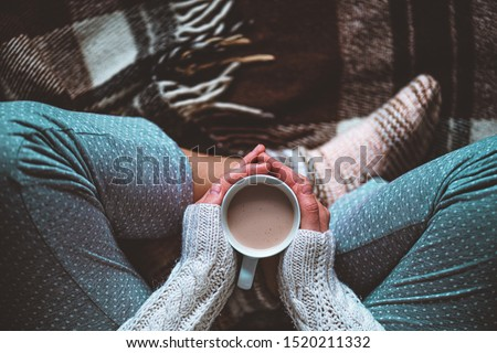 Cozy woman in knitted winter warm socks and in pajamas holding a cup of hot cocoa during resting on checkered plaid blanket at home in winter time. Cozy time and winter drinks. Top view  Сток-фото ©