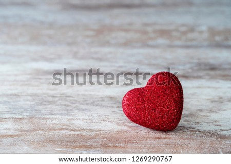 Cozy wooden background, with a red heart with glitter in the center, love concept, for Valentine's Day, Mother's Day, Father's Day, Christmas, holidays. #1269290767