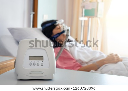 Cpap machine is treating senior patient woman wearing Cpap mask sleeping smoothly without snoring in hospital room.Obstructive sleep apnea therapy. Foto stock ©