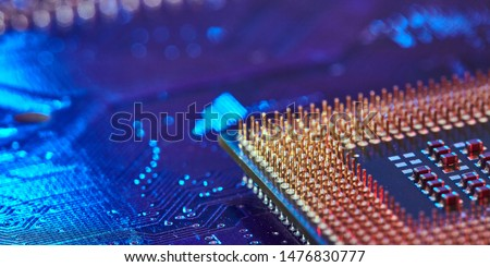CPU desktop with the contacts facing up lying on the motherboard of the PC. the chip is highlighted with blue light. Technology background