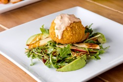 Crab cake. Crab cake served with spicy rémoulade sauce on top of a mixed green salad. Jumbo crab meat mixed with garlic, onions, spices and fried in butter. Classic American restaurant appetizer.