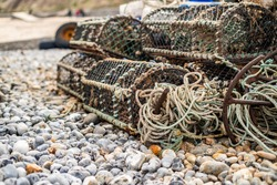 Crab fishing gear left on Cromer beach comprising fishing pots, rope, metal anchor and fenders. Shallow depth of field, selective focus and bokeh