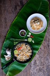 Crab fried rice in white bowl and black pan on banana leaf background, wooden board, fried rice is Asian food, top view - Thai style concept.