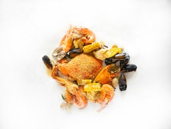 Crab in the bag seafood boil flatlay. Louisiana style Crab on white table with copy space. Crab, prawns, mussels, seafood top down shot.