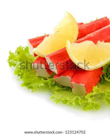 Crab sticks on lettuce leaves with lemon, isolated on white