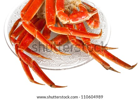 Crablegs cooked and placed on a fancy clear plate on a white background