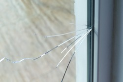 Crack on the glass at a residential house. Plastic window is damaged by cracks.