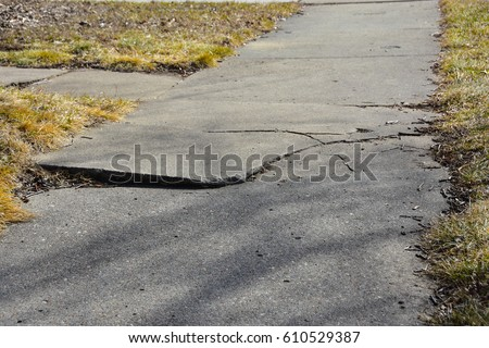 Cracked and broken section of sidewalk in city.