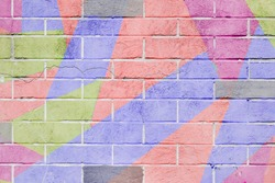 Cracked and scratched wall with graffiti. Abstract detail of urban street art design close-up, pastel colors. Modern stylish pattern, for backgrounds. Aerosol pictures