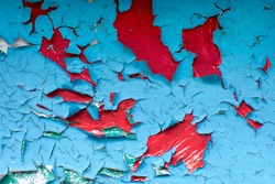 Cracked blue paint covers the red metal wall. The paint is chipped, cracked, and fallen off due to environmental exposure. Bright red spots formed. Close-up photo, cropped.