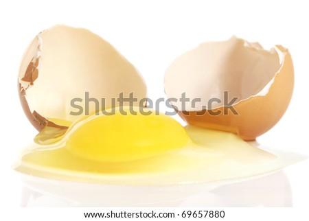 Cracked brown egg, with yolk spilling on white background