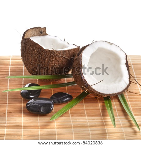 Cracked coconut with leaves and spa stones