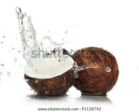cracked coconut with splashing water - stock photo