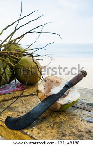 cracked coconuts and machete on table