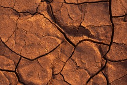 Cracked earth texture of ground, broken and rough surface red mud clay soil in summer season, crack ground floor on arid drought environment and hot weather in nature, light on top photo for graphic