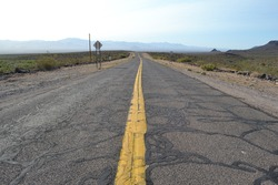 Cracked endless road with yellow double line in the Arizona desert, USA