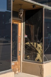 Cracked glass window pane by shop door looking like rioters have tried to enter the store