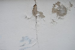 cracked house wall affected by rains and earthquakes. former crack white house wall. Old wall of a building or house with cracks. cement floor