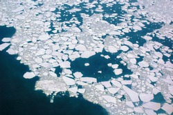 Cracked ice floes drifting on blue ocean water