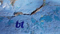 Cracked painted surface of old cement wall covered with many layers of blue flaking paint and cutout blue Cyrillic letter Y closeup