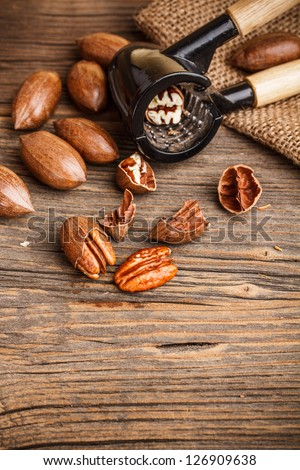 Cracked pecan nuts on rustic wooden table