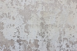 Cracked peeling paint on a stucco of a building facade with visible gray base underneath