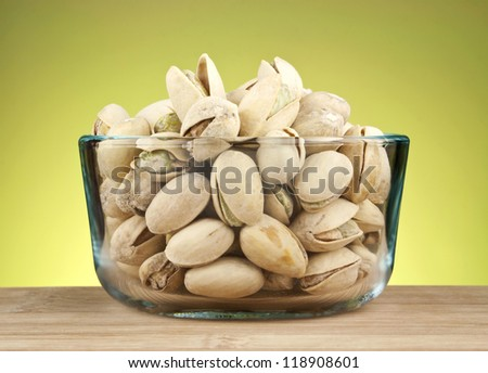 Cracked pistachio nuts in glass bowl on green background.
