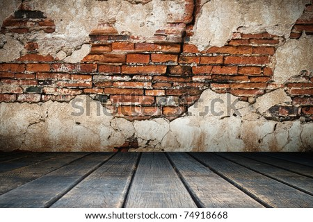 Cracked plaster of old brick wall and wood floor