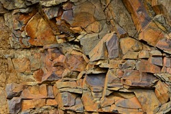 Cracked red rock. Rusty stones with sharp corners and fine red gravel. Plates of red, black and brown stone. Stone ready for mining.