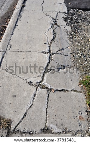 Cracked Sidewalk in Urban Area - stock photo