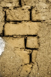 Cracked wall made up of mud-brick and soil