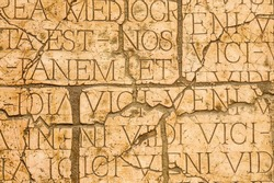 Cracked wall with Latin inscriptions and Roman letters, marble background.