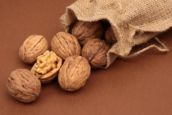 cracked walnuts and walnuts spilled on a brown background
