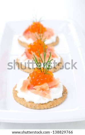 crackers with cream cheese, salted salmon and red caviar on the white plate