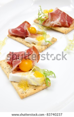 Crackers with goat cheese, apricot spread, and yellow pear tomatoes wrapped to prosciutto