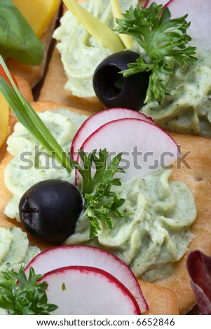 Crackers with spread, vegetables, and garnish