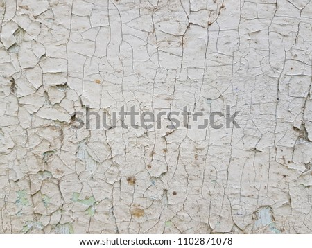 Cracking and peeling paint on a wall. Vintage wood background. Old board with Irradiated paint #1102871078