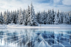 Cracks on the surface of the blue ice. Frozen lake in winter mountains. It is snowing. The hills of pines. Carpathian Ukraine Europe.