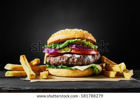 Craft beef burger and french fries on wooden table isolated on black background.