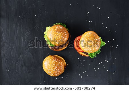 Craft beef burgers with vegetables. Flat lay on black textured background with sesame seeds.