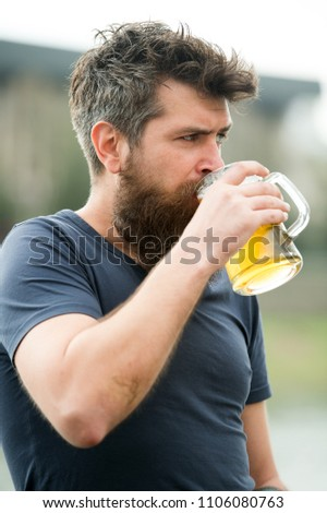 Craft beer concept. Man with long beard looks relaxed. Man with beard and mustache on strict or serious face, light background, defocused. Bearded man holds beer mug, drinks beer outdoor. #1106080763