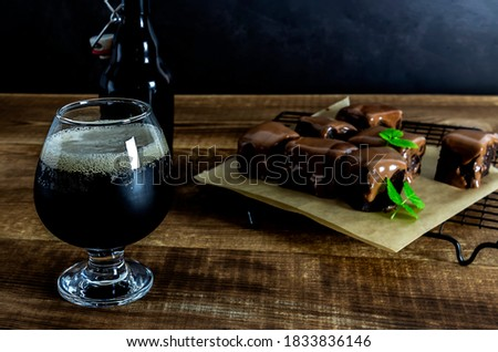 Craft beer imperial stout with sweet chocolate brownies on the wooden table. Stock photo ©