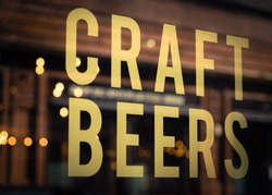 Craft Beers Sign in Pub Window With Reflection of Lights in Glasgow,  Scotland